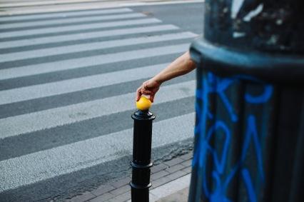 hand on yellow ball at crosswalk