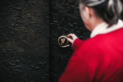 secrets door handle red coat lady focus hands