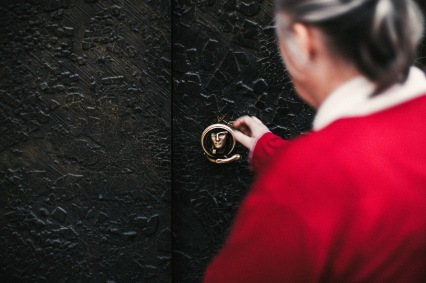 secrets door handle red coat lady focus hands