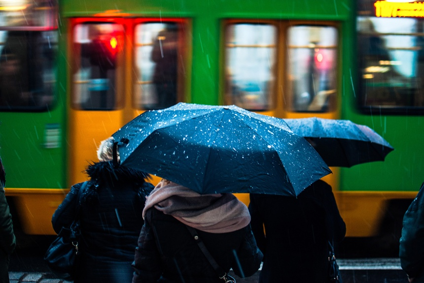 Group-of-people-waiting-to-cross-street-umbrellas-and-snow-tram-passing-small